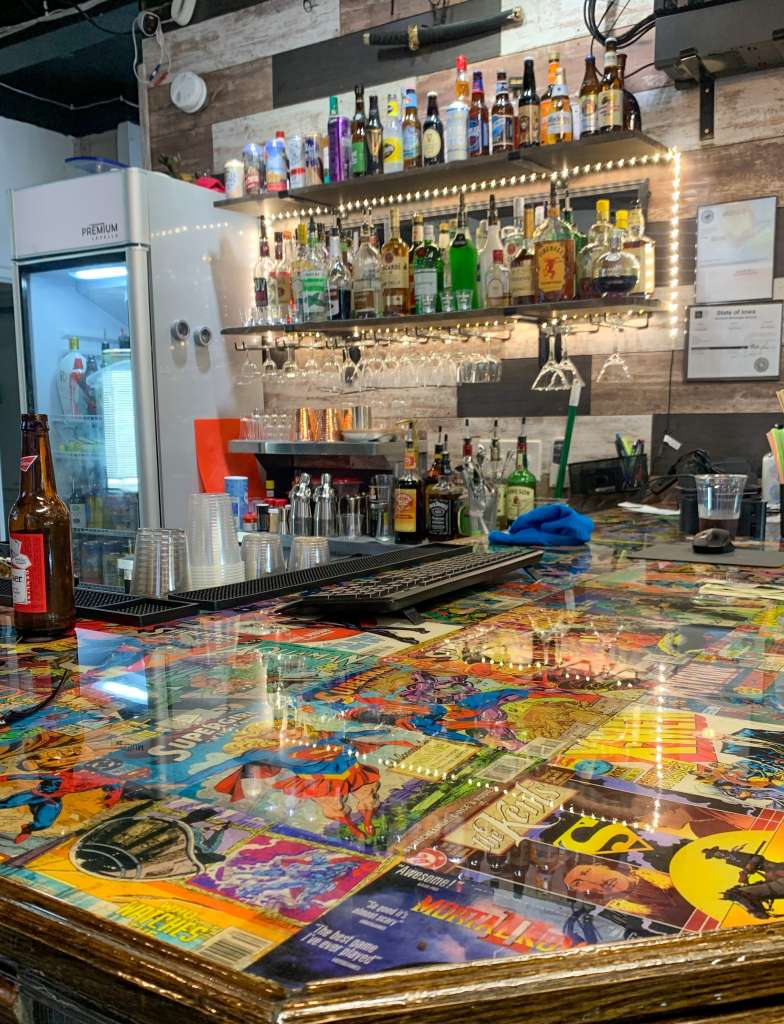 Picture of a bartop featuring a collage of comics and bottle of liquor and alcholo behind the bar
